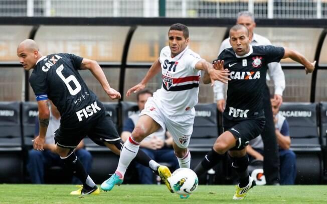 O lateral Douglas, do São Paulo, tenta fugir  de Fábio Santos e Emerson Sheik