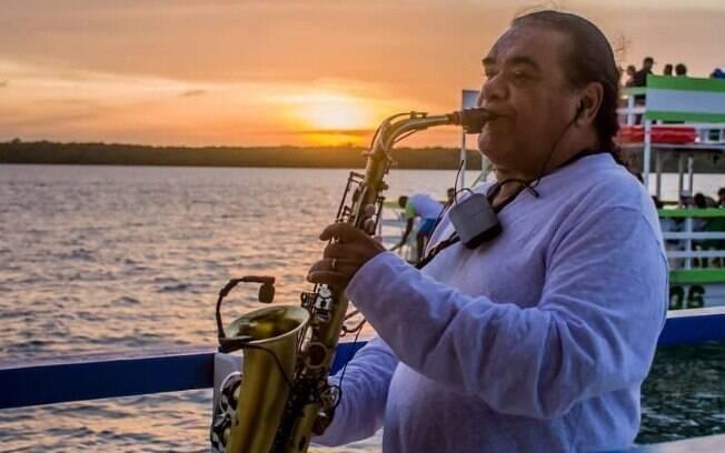 Artista Jurandy do Sax tocando durante o pôr do Sol na praia do Jacaré, em João Pessoa