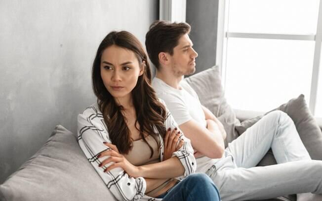 Um casal está sentado no sofá, e os dois estão de braço cruzado; a mulher está de costas para ele e encara o vazio; o homem é visto de perfil e está olhando para frente