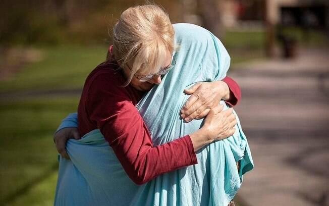 Mãe e filha precisaram de um lençol para se abraçarem em meio a pandemia da Covid-19