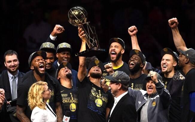 Jogadores do Golden State Warriors levantam o troféu Larry O'Brien de campeão da NBA pelo segundo ano consecutivo