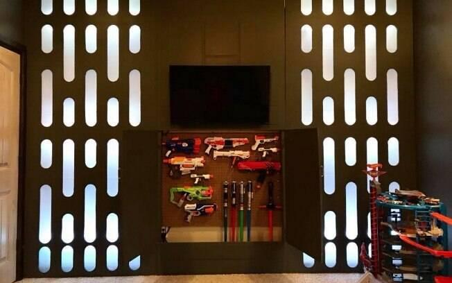 A parede oposta à cama é coberta por placas metalizadas e se abre para um 'arsenal de armas'