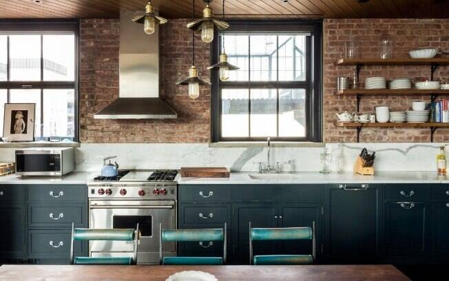 Com tijolos e gabinetes azul-petróleo, a cozinha do apartamento lembra a da série