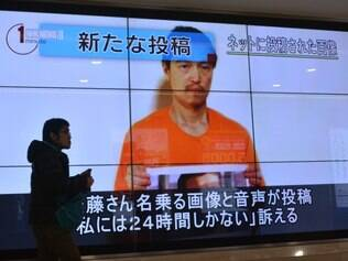 A pedestrian looks at a large screen in Tokyo on January 28, 2015 showing television news reports about Japanese hostage Kenji Goto who has been kidnapped by the Islamic State group. Japan has asked Jordan for help after the Islamic State jihadist group threatened to kill a Japanese journalist and a Jordanian pilot within 24 hours unless Amman frees a jailed female militant. AFP PHOTO / KAZUHIRO NOGI