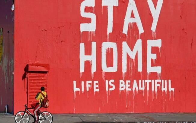 """Um homem anda de bicicleta passando por um mural que diz """"Fique em Casa/A Vida é Bela"""" durante a pandemia de coronavírus (Covid-19)"""