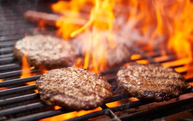 Hambúrgueres sendo grelhados na brasa de uma churrasqueira.