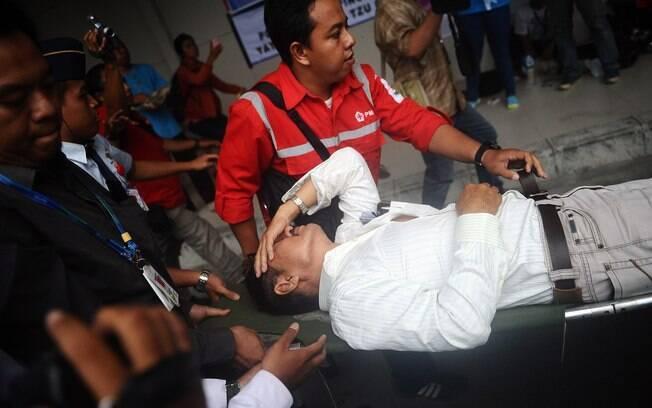 Parente de passageiros do voo QZ8501 da AirAsia recebe atenção médica após saber que corpos foram encontrados no Mar de Java . Foto: Robertus Pudyanto/Getty Images
