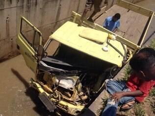 Após o caminhão cair no córrego, populares ajudaram o motorista que ficou preso às ferragens