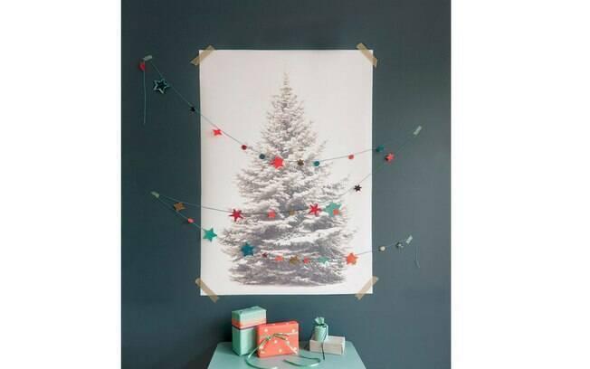 Combinação bem pensada: a parede azul com a gravura em preto e branco de um pinheiro recebe os adornos coloridos para dar o tom de alegria e celebração