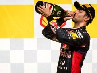 Red Bull driver Daniel Ricciardo of Australia drinks champagne as he stands on the podium after he won the Belgian Formula One Grand Prix in Spa-Francorchamps, Belgium, Sunday, Aug. 24, 2014. Red Bull driver Daniel Ricciardo of Australia won the race, Mercedes driver Nico Rosberg of Germany finished second and Williams driver Valtteri Bottas of Finland third. (AP Photo/Geert Vanden Wijngaert)