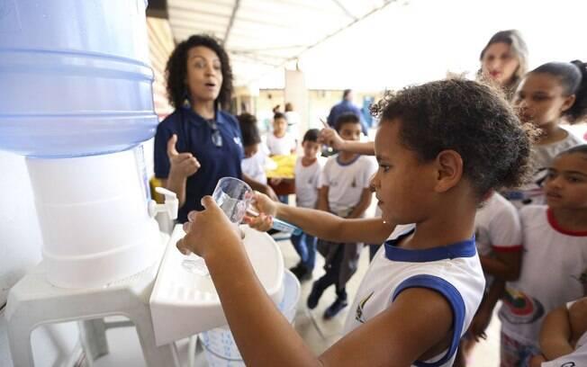 Criança pegando água mineral em bebedouro