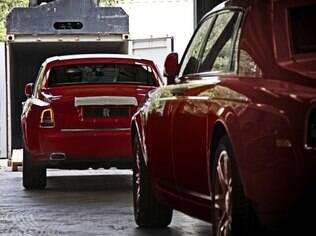 Fila de sedãs Rolls-Royce Phantom se forma. Os carros entram em conteiners para serem entregues ao bilionário que os comprou