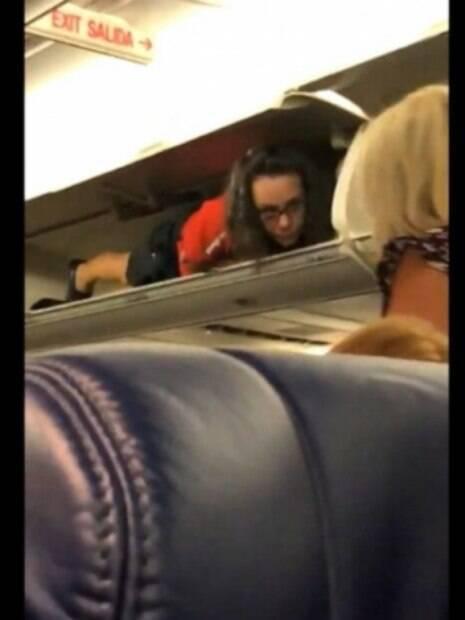 comissária de voo entra no bagageiro do avião