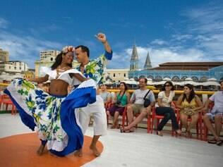 Dança de carimbó em um passeio de barco pela orla de Belém e ao fundo, o famoso Mercado Ver-o-Peso