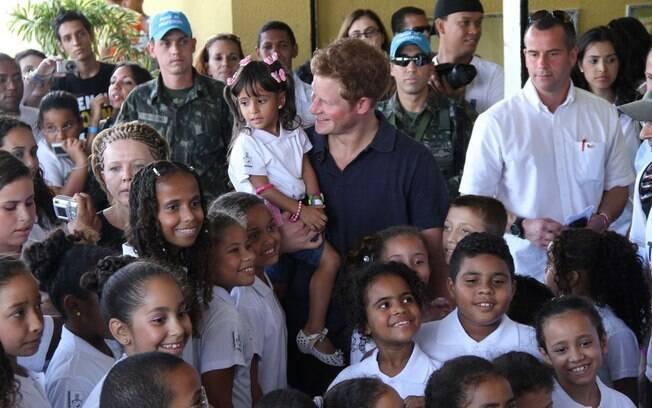 Com uma das meninas no colo, príncipe Harry posou para as fotos com as crianças do Complexo do Alemão
