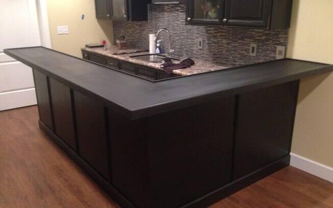 A bancada foi comprada pronta e, em casa, ele pintou a madeira de preto, instalou o móvel e começou a colocar as tampas