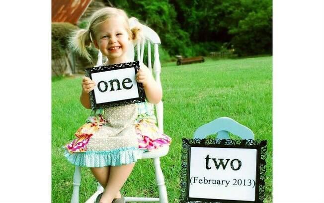 Com uma placa, a garota mostra que está esperando um irmão