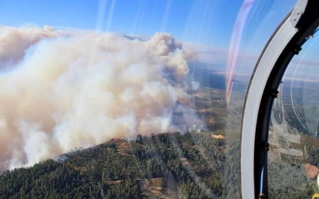 Coluna de fumaça sobre floresta na Califórnia; incêndios são os piores da história