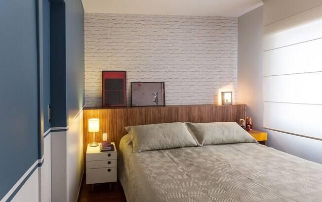 Um quarto aconchegante faz toda a diferença. A cabeceira em baú de madeira recebe papel de parede imitando tijolinho que conta com os quadros apoiados para finalizar a co