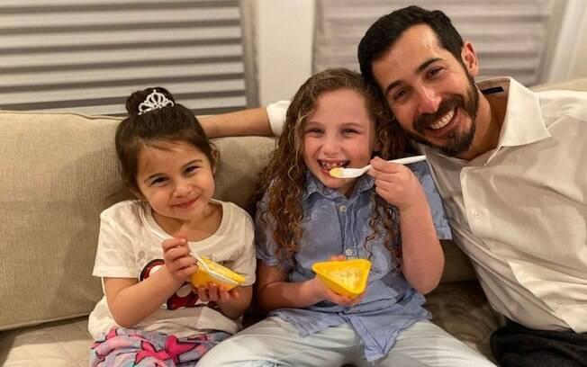 Fotografia do pai, junto com as duas filhas, enquanto as duas crianças comem.