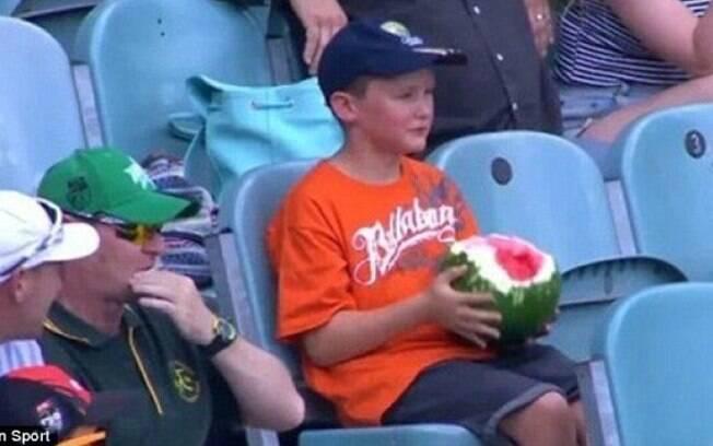 Menino é flagrado comendo uma melancia inteira na arquibancada de partida de críquete