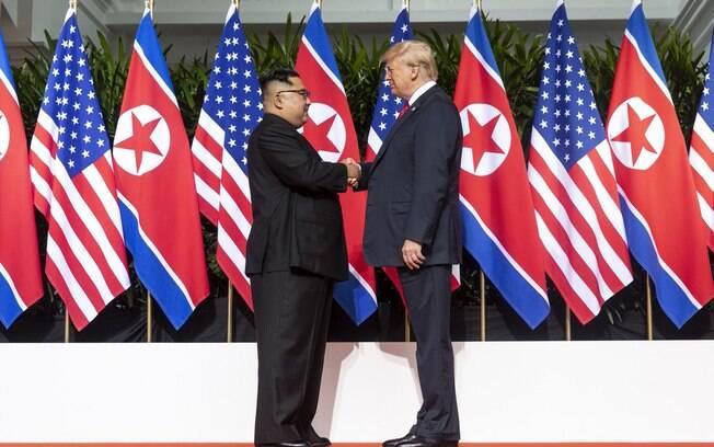 Donald Trump e Kim Jong-un se apertam as mãos antes da reunião histórica