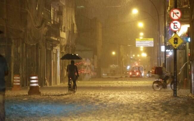 Rua do Senado, no Centro: ciclista adaptou guarda-chuva à bicicleta para minimizar transtorno do temporal