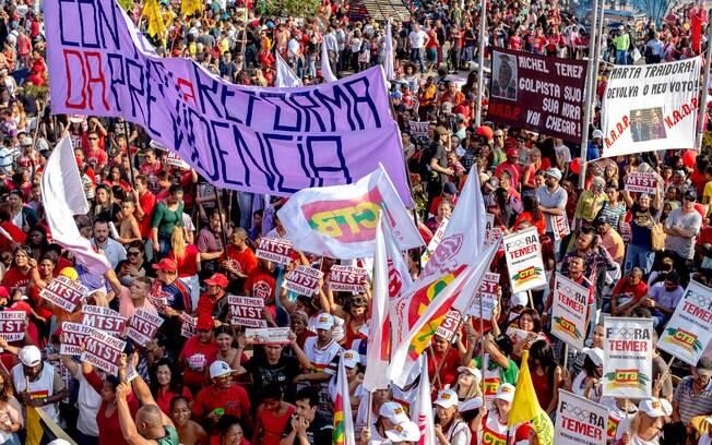 As imagens mostram manifestantes com faixas que exibem frases contrárias ao presidente em exercício, Michel Temer