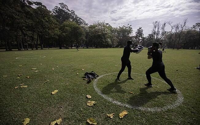 Pessoas praticam esportes em área delimitada para o distanciamento social