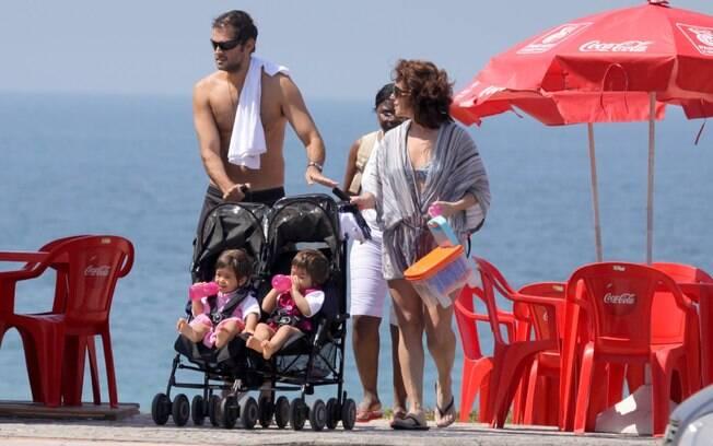 Leonardo e Giovanna deixam a praia com as meninas no carrinho