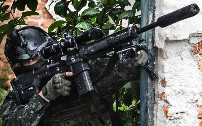 Note que a mão esquerda do Atirador de Precisão do COE dá apoio ao bipé do rifle, mas não toca no corpo do rifle para evitar a transmissão de possíveis vibrações do seu corpo para a arma e que possam afetar a trajetória do tiro.