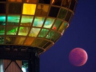 A lunar eclipse dips beneath the Sunsphere in Knoxville, Tenn. on Wednesday, Oct. 8, 2014.  The moon appears orange or red, the result of sunlight scattering off Earth's atmosphere. This is known as the blood moon.(AP Photo/Knoxville News Sentinel, Adam Lau)