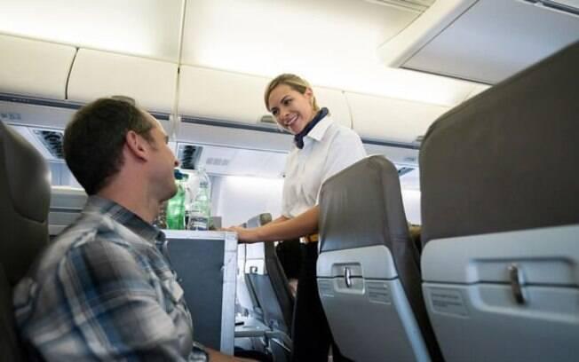 Comissária de bordo oferecendo bebidas para um passageiro no avião.