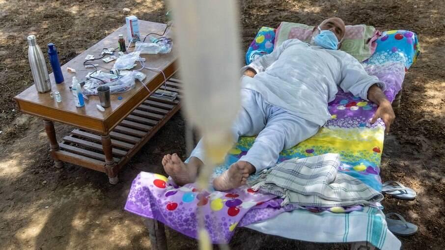 Paciente recebe tratamento embaixo de árvore na Índia