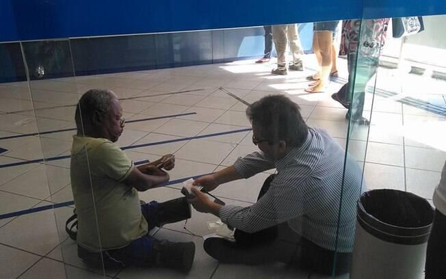O gerente Luís Cláudio se sentou no chão do banco para atender um cliente