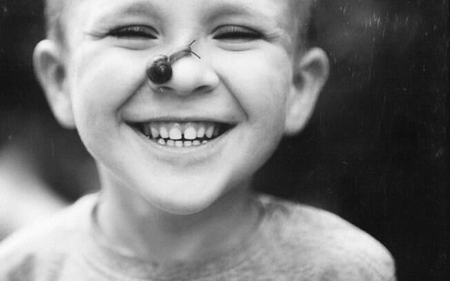 Criança sorrindo enquanto caracol rasteja pelo seu narizinho.