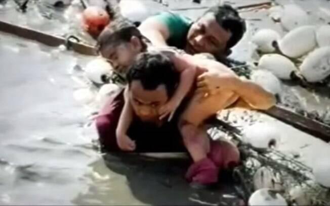 Homem ajuda criança a sair de local alagado após tsunami da Indonésia (arquivo). Foto: Reprodução/Youtube