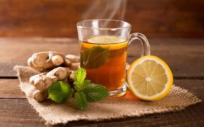 Xícara de chá de gengibre com limão e menta cercada por gengibre, limão e folhas de menta