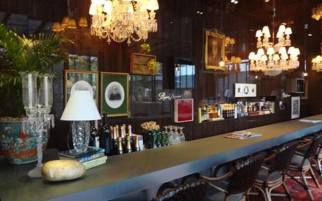 Molduras vintage na cor dourada reforçam a atmosfera clássica impressa no Bar do Relógio, de José Roberto Moreira do Valle