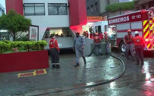 Bombeiros trabalham em prédio que ficou inundado pela chuva