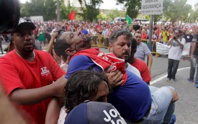 Manifestante da Central Única dos Trabalhadores é levado por colegas após briga com anti-PT