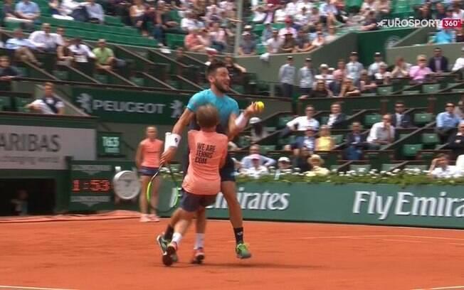 O tenista bósnio Damir Dzumhur se choca com jovem gandula durante partida de Roland Garros