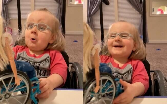 Pequena Ella parece, ao mesmo tempo, espantada e feliz ao ganhar uma boneca que, assim como ela, usa cadeira de rodas