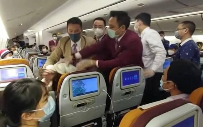pessoas imobilizando homem em avião