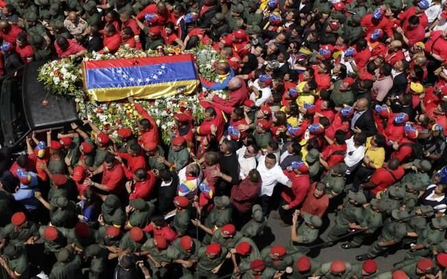 Pessoas caminham ao lado de caixão de Hugo Chávez coberto com bandeira venezuelana em Caracas (06/03)