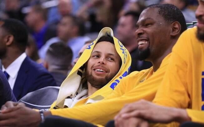 Stephen Curry ri ao lado de Kevin Durant durante partida do Golden State Warriors