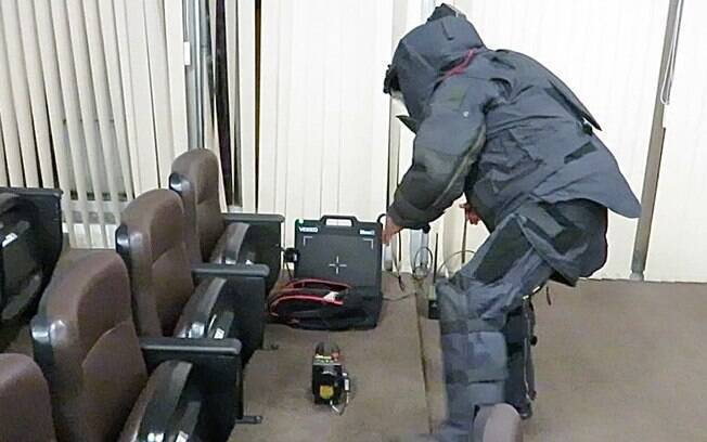 Explosivista coloca o transmissor de raio-x na frente a mochila, a placa receptora atrás e conecta o equipamento de transmissão que irá enviar as imagens para a equipe de comando, fora da sala. Note que as mãos do Explosivista não possuem nenhuma proteção, para que ele não perca a sensibilidade de manipulação