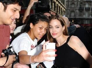 Angelina Jolie posa com fã na première de
