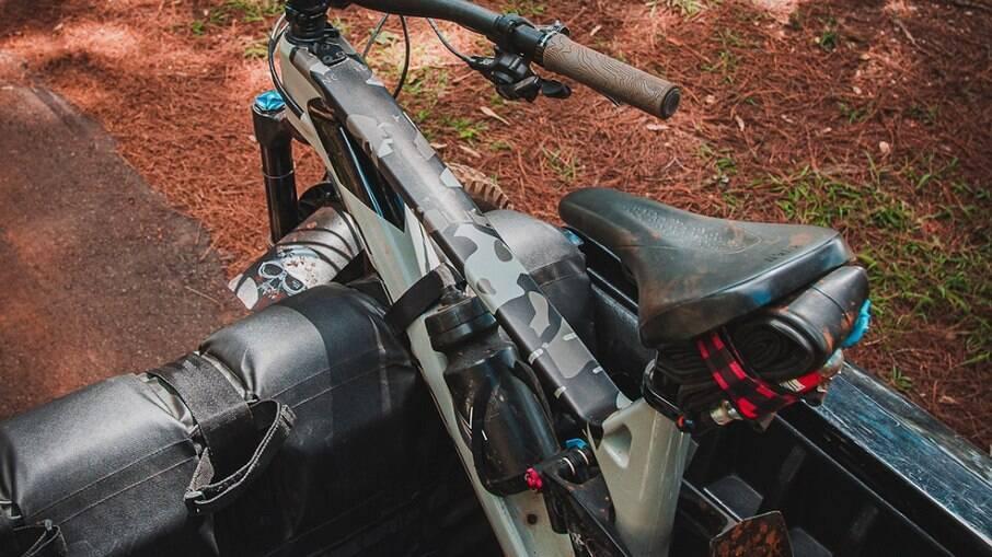 A bike vai presa por cintas que não riscam o quadro e nem o garfo da bicicleta.