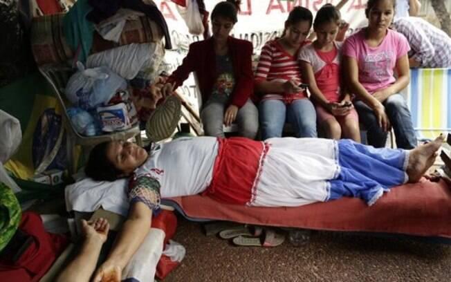 Mulher é crucificada em protesto em Assunção, no Paraguai. Foto: AP Photo